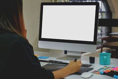 Designer working with digital tablet and desktop computer at desk. Side view of an artist drawing something on graphic tablet at the office.  Blank screen Stock Images