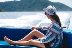 Side view. asia woman sitting on back of boat and looking scener Stock Images