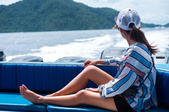 Side view. asia woman sitting on back of boat and looking scener Royalty Free Stock Photo