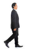 Side view Asian business man walking. Full length side view of attractive young Southeast Asian businessman walking, isolated on white background Royalty Free Stock Image