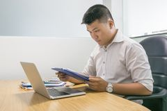 Asian businessman checking financial number on report royalty free stock photos
