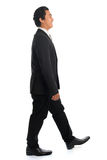 Side view Asian businessman walking Royalty Free Stock Images