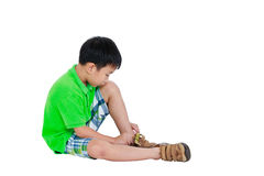 Side view of asian child put leather shoes on. Isolated on white Stock Photos