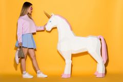 side view of asian female model in sunglasses holding handbag and touching decorative unicorn on yellow stock images