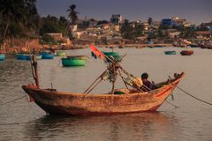 Side View Asian Fisherman Sits in Boat by Bank against Village Royalty Free Stock Images