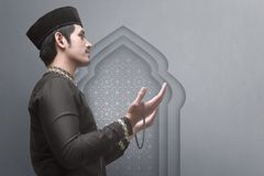 Side view of asian muslim male raising hand while praying stock photo