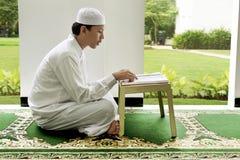 Side view of asian muslim man reading holy book koran Royalty Free Stock Photos