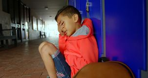 Side view of Asian schoolboy sitting alone with hands covering his face in school corridor 4k stock video footage