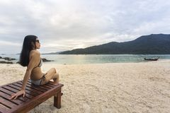 Asian woman sitting on wooden chair at the beach. stock photography
