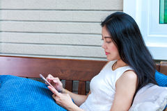Side view of asian woman typing text messages on smart phone. Royalty Free Stock Photography