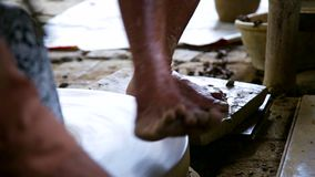 Side view assistant rotates potter wheel by bare foot. Close side view potter assistant rotates pottery wheel by bare foot standing on board in country workshop stock video