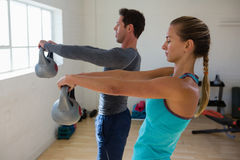 Side view of athletes lifting kettlebells. In health club Stock Photography