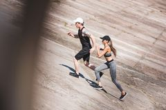 Couple jogging on slabs. Side view of athletic couple jogging together on slabs Royalty Free Stock Images