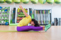 Side view of athletic female working out on mat in gym, bending and stretching her back leg muscles Royalty Free Stock Image