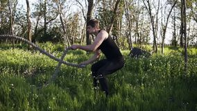 Side view of an athletic male working out using battle ropes. Crossfit. Swing. Green park. Black sport clothes.  stock footage