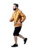Side view of athletic man jogging in jacket looking up. Toned desaturated full body length portrait isolated on white studio background Stock Photography