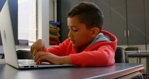 Side view of attentive Asian schoolboy studying with laptop in classroom at school 4k stock video