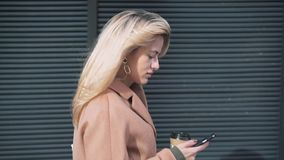 Side view of blonde woman with coffee walking and web surfing. Side view of attractive blonde woman wearing beige coat and holding a cup of coffee to go walking stock video