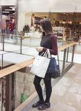 Side view of stylish attractive woman standing in interior of the shopping mall with shopping bags stock photos