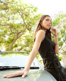 Businesswoman leaning on car with phone. Royalty Free Stock Photography