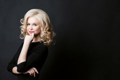 Side view of attractive curly blonde woman after beauty salon with stylish and volume haircut. Girl posing at camera and holding f Royalty Free Stock Photography