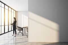 Businessman walking in modern meeting room. Side view of attractive european businesswoman with laptop standing in modern meeting room interior with copy space royalty free stock image