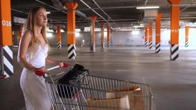 Pretty woman carrying shopping cart in parking. Side view of attractive female buyer walking with shopping cart through underground parking after shopping stock video