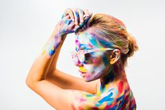 Side view of attractive girl with colorful bright body art and sunglasses. Isolated on white stock images