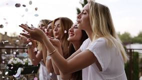 Side view. Attractive, smiling girls stand in a row and blow confetti from the hands. Hen party concept. Standing stock video footage