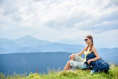Woman hiker hiking on grassy hill, wearing backpack, using trekking sticks in the mountains. Side view of attractive woman backpacker sitting on grassy hill with stock photos
