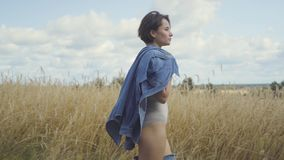 Side view of an attractive woman wearing bodysuit with short hair holding jeans jacket on her shoulder walking through. The wheat field. Connection with nature stock video footage