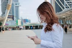 Side view of attractive young Asian business woman looking mobile smart phone in her hands at urban building city background. Side view of attractive young Stock Image