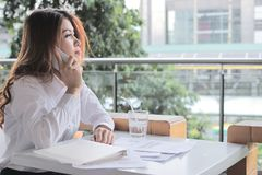 Side view of attractive young Asian business woman talking on mobile smart phone against partnership on the desk in office with co. Side view of attractive young Royalty Free Stock Image