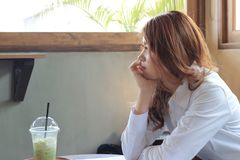Side view of attractive young Asian business woman waiting something in coffee shop Royalty Free Stock Image