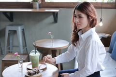 Side view of attractive young Asian woman eating brownie dessert with fork in coffee cafe background. Side view of attractive young Asian woman eating brownie Stock Photos