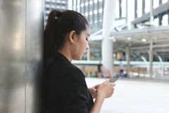 Side view of attractive young Asian woman holding mobile smart phone on the street of city. Social network concept royalty free stock photo