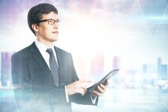 Network and success concept. E view of attractive young european businessman using cellphone on blurry city background. Network and success concept royalty free stock photography