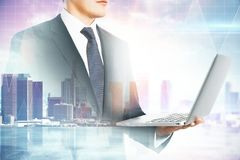 Communication and success concept. E view of attractive young european businessman using laptop on blurry city background. Communication and success concept stock photo