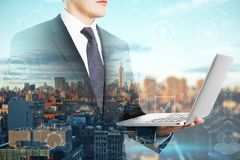Network and success concept. E view of attractive young european businessman using laptop on blurry city background. Network and success concept. Double exposure stock photography