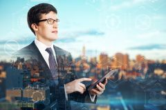 Network and success concept. E view of attractive young european businessman using smartphone on blurry city background. Network and success concept. Double royalty free stock image