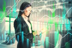Stock and trade concept. Side view of attractive young european businesswoman using tablet with glowing forex chart on blurry office interior background. Stock royalty free stock photos