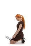 Woman kneeling reading her laptop stock images