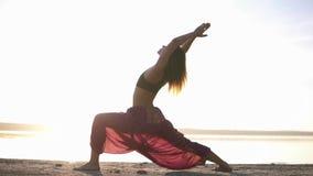 Side view of attractive young woman practicing yoga in warrior pose Virabhadrasana on seashore. Light sun haze.  stock footage