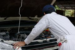 Side view of automotive mechanic in white uniform diagnosing engine under hood of car at the repair garage. Side view of automotive mechanic in white uniform Royalty Free Stock Photo