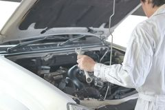 Side view of automotive mechanic in white uniform with wrench diagnosing engine under hood of car at the repair garage. Side view of automotive mechanic in Royalty Free Stock Photography