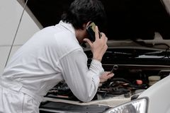 Side view of automotive repairman in uniform talking on phone and examining engine under hood of car at the repair garage. Side view of automotive repairman in royalty free stock images