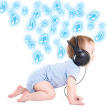 Side view of baby boy toddler listening music with headphones ov Stock Images