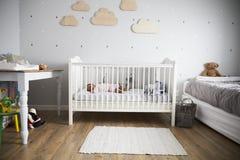 Side View Of Baby Girl Sleeping In Nursery Cot Stock Photo