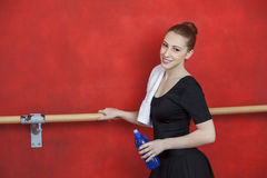 Side View Of Ballerina Holding Water Bottle. Side view portrait of young ballerina holding water bottle against red wall in dance studio Stock Photo