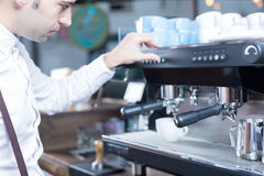 Side view of bartender pushing the button on coffee machine Royalty Free Stock Photos